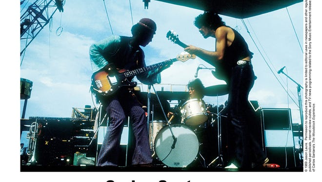 Carlos Santana, right, on guitar, and Michael Shrieve, center, on drums, perform at the Woodstock Music and Art Fair in August 1969.