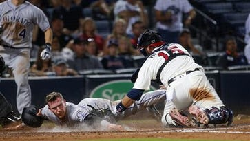 Colorado Rockies' Trevor Story (27) beats the tag from Atlanta Braves catcher A.J. Pierzynski (15) as he scores the go-ahead run on a Mark Reynolds ground ball during the ninth inning of a baseball game Saturday, July 16, 2016, Atlanta. Braves shortstop Erick Aybar was charged with an error.