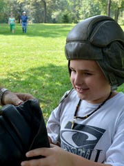 Mason Coffey of Greenville tries on hats and helmets from World War II with assistance from Jim Belcher who mans a display at the U.S. Military History Weekend in 2013.