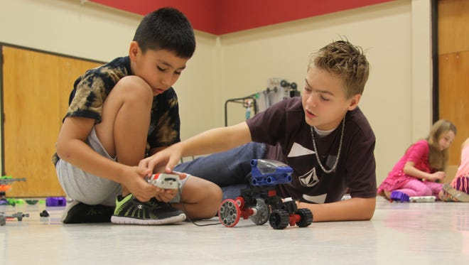 Jaylon Campos, 8, and Brendon Cuevas, 11, test to see if their model works at Follow Me Robot summer camp, June 26, 2017. The students worked in a team of two to build a model and connect it to a remote control.