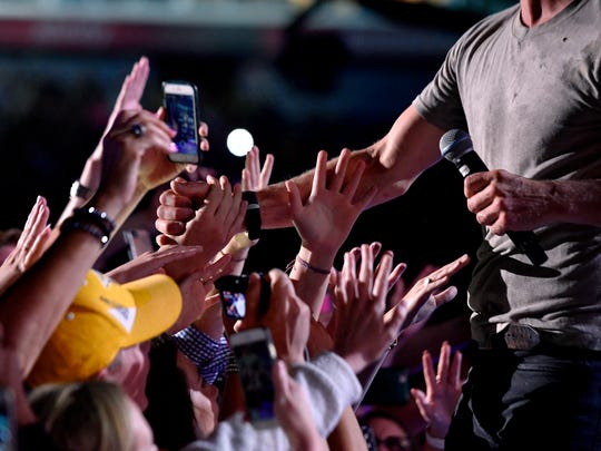 Fans greet Dierks Bentley as he performs at Nissan Stadium on the first day of the 2017 CMA Music Festival on June 8, 2017, in Nashville.