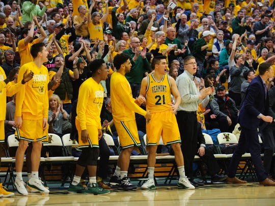 The Vermont bench celebrates during the America East