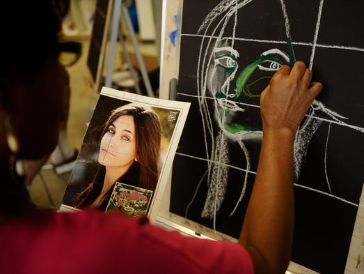 Nailah Jumoke uses a photo for reference during a drawing class at the North Hollywood Senior Arts Colony, in North Hollywood, Calif.