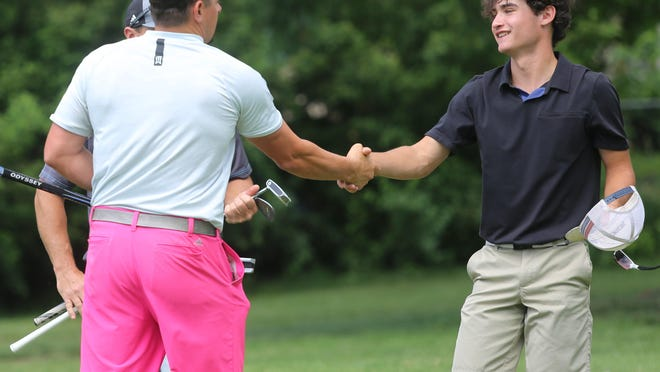 Adam Head (left) gets a congratulatory handshake from Luke Leonetti after beating Leonetti in Sunday's TGA City Match Play championship match. A hot putter carried Head to a 6&4 victory and his first TGA Match Play title.