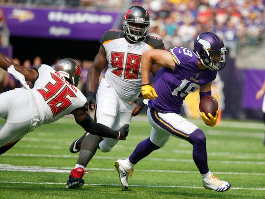 Minnesota Vikings wide receiver Adam Thielen (19) runs from Tampa Bay Buccaneers defenders Robert McClain, left, and Clinton McDonald, rear, after catching a pass during the first half of an NFL football game, Sunday, Sept. 24, 2017, in Minneapolis. The Vikings won 34-17. (AP Photo/Bruce Kluckhohn)
