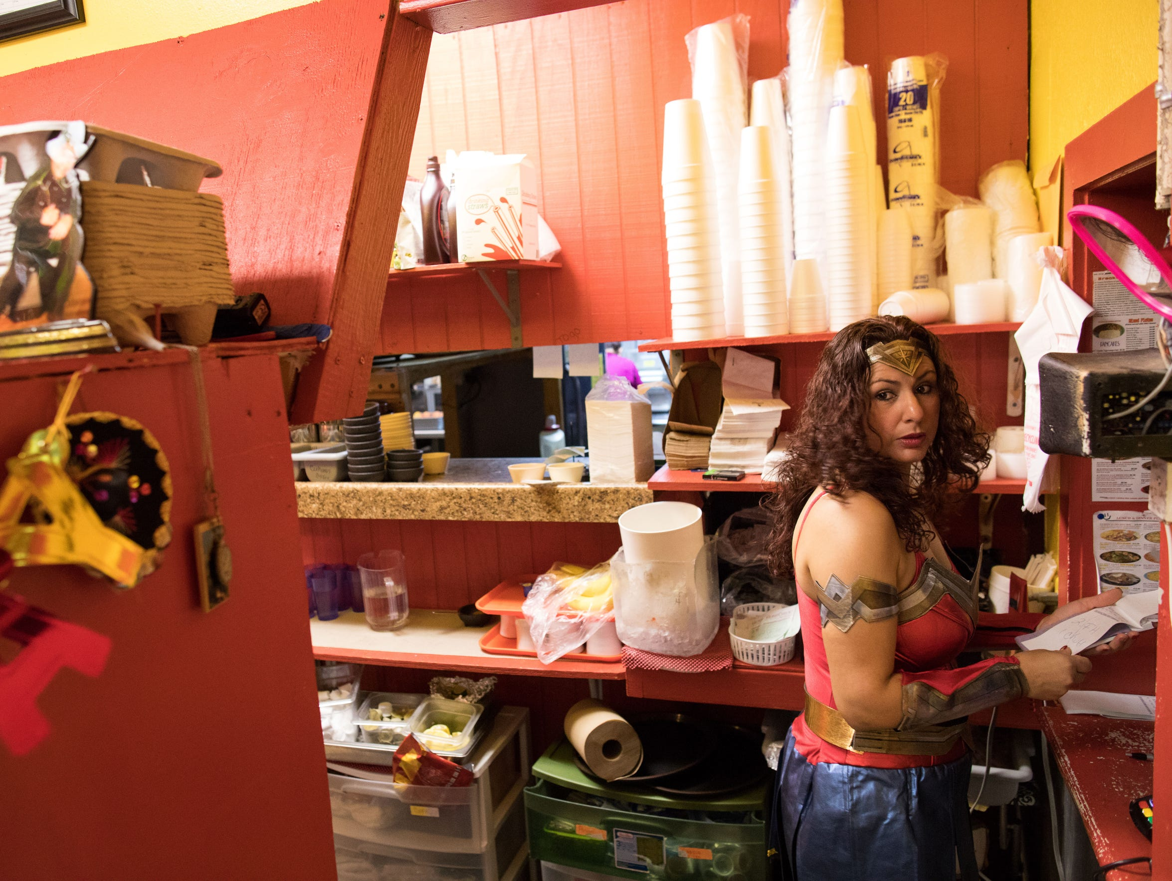 Monica Rocha Alcarez, clad in a Wonder Woman Halloween costume, looks over to the front door of Monica's Restaurant on Oct. 31, 2017. She was brought over from Mexico at the age of four. She's earned a business degree and since becoming a DACA recipient she's been able to become a business owner.