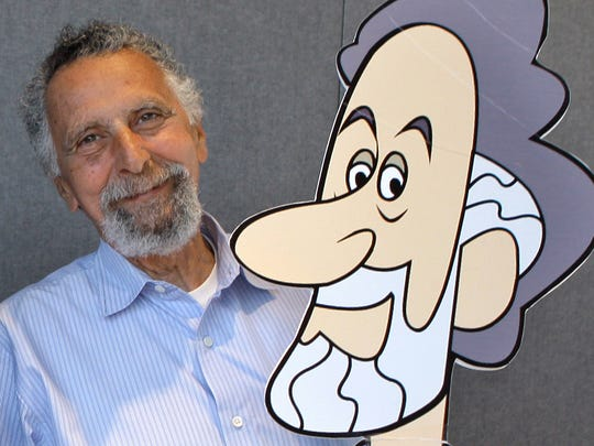 Tom Magliozzi poses with a caricature of himself in