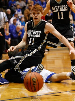 Corydon's Bronson Kessinger, #41, gets tied up with a North Harrison player as they chase a loose ball during their game at the North Harrison High School. Mar. 5, 2014