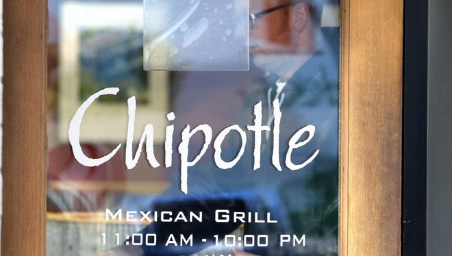 A customer leaves a Chipotle restaurant with food in Portland, Ore., on Nov. 11, 2015.  Chipotle started reopening its restaurants in the Pacific Northwest on Wednesday after an E. coli outbreak sickened about 45 people, a high-profile example of foodborne illnesses that are more common than the public realizes, health experts say. Forty-three outposts of the Mexican food chain in Washington state and the Portland, Ore., area were closed at the end of October because of the outbreak that hospitalized more than a dozen people.