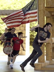 """JASON CLARK / COURIER & PRESS Matt Krieg runs with the American flag while playing Thomas Lincoln during a rehearsal of """"A. Lincoln: A Pioneer Tale"""" at Lincoln Amphitheatre in Lincoln State Park in Lincoln City Ind., Wednesday."""