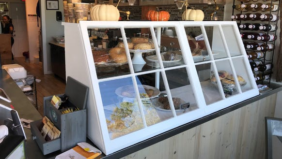 A vintage window repurposed as a pastry case adds a