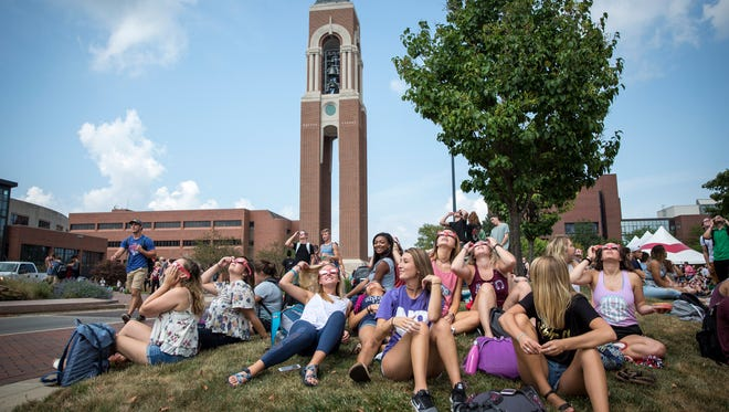 Ball State students and faculty gather on the University Green just next to Shafer Tower on Ball State's campus for an eclipse watch party. Due to a power outage over 1,000 people crowded Ball State's main avenue to see the event.