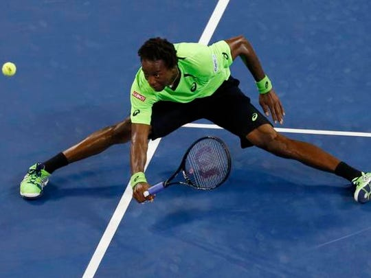 Gael Monfils of France falls to the court as he comes to the net to try to make a return in the fourth set to Roger Federer of Switzerland during their quarter-final men's singles match at the 2014 U.S. Open tennis tournament in New York, September 4, 2014.