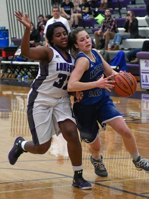 Harper Creek's Faith Hayes (21) drives past Lakeview's Jaida Boggerty (32) during second quarter of play Tuesday night.