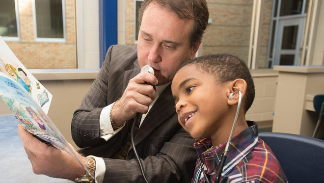 Gary Swisher II, CLM, Chief Administrative Officer at Clark, Partington, Hart, Larry, Bond & Stackhouse, uses a stethoscope while reading with Vachaun Simpkins at Global Learning Academy.
