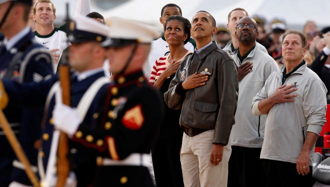 President Barack Obama and first lady Michelle Obama join Michigan State coach Tom Izzo, right, the men's basketball team as they watch a flyover from the flight deck of the USS Carl Vinson before the Carrier Classic NCAA basketball game between Michigan State and North Carolina, Friday, Nov. 11, 2011, in Coronado, Calif.