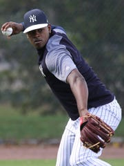 Luis Severino throws the ball to first as the pitchers practiced playing defense.
