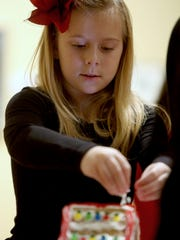 """Sydney Clark, 8, sprinkles """"snow"""" on the roof of her gingerbread house during a past gingerbread family workshop at Minnetrista."""