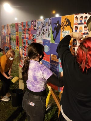 High school students decorate the Holmes Playground message wall with posters they designed. The wall was taken down by vandals the next day.