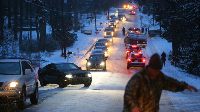 Dozens of motorists are stranded on Womack Road as dropping temperatures turn the hill into a sheet of ice on Jan. 28, 2014, in Dunwoody, Ga.