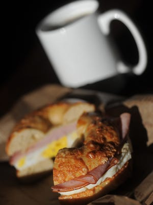 Classic egg breakfast sandwich with ham and swiss on an Asiago bagel along with a cup of dark roast coffee from Caribou Coffee and Einstein Bros. Bagels on Thursday, Dec. 31, 2015.