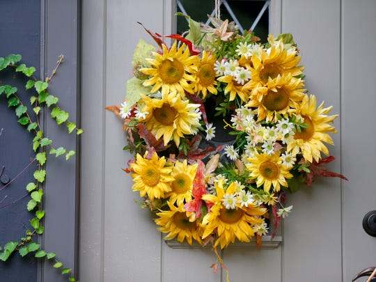 A floral wreath hangs on the front door of the porch of florist Deb Fowler.