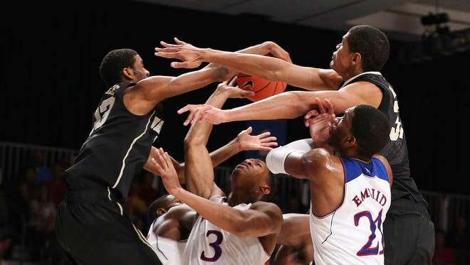 Kansas guard Andrew White III battles for a loose ball with Wake Forest's Aaron Rountree III (left) and Andre Washington (right).