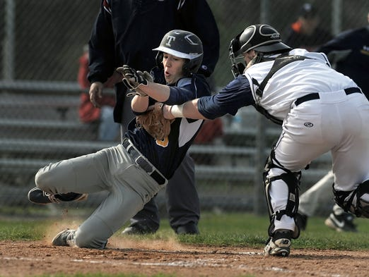 Webster Thomas' Matt Carey, left, is tagged out at home by Victor catcher Brett Prong.
