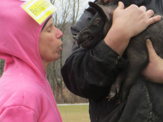 Hinesburg special educator Jen Bradford kisses a pig as part of the fundraiser.