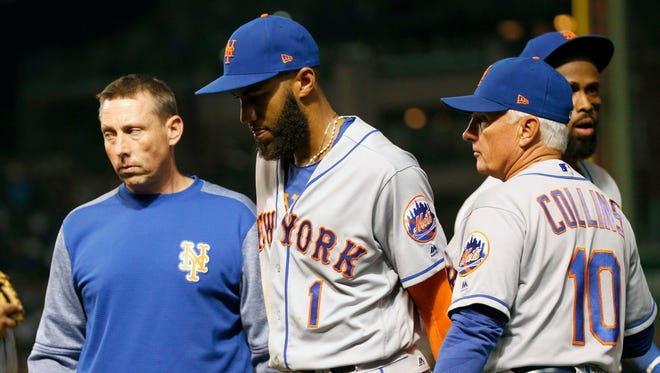 New York Mets' assistant trainer Brian Chicklo, left, and manager Terry Collins (10) pull Amed Rosario from the game in the middle of the fifth inning of a baseball game against the Chicago Cubs Thursday, Sept. 14, 2017, in Chicago.