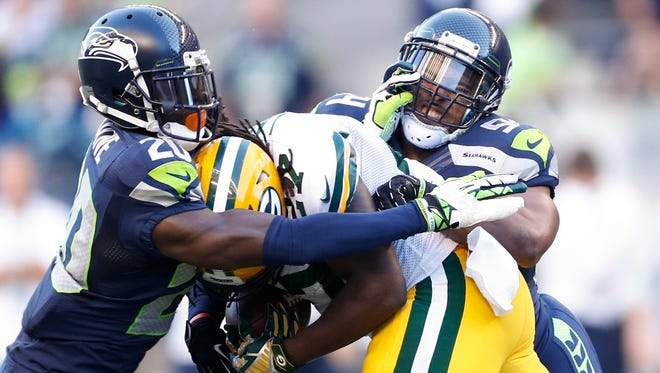Seattle Seahawks cornerback Jeremy Lane (20) and middle linebacker Bobby Wagner (54) tackle Green Bay Packers running back Eddie Lacy (27) during the second quarter at CenturyLink Field.