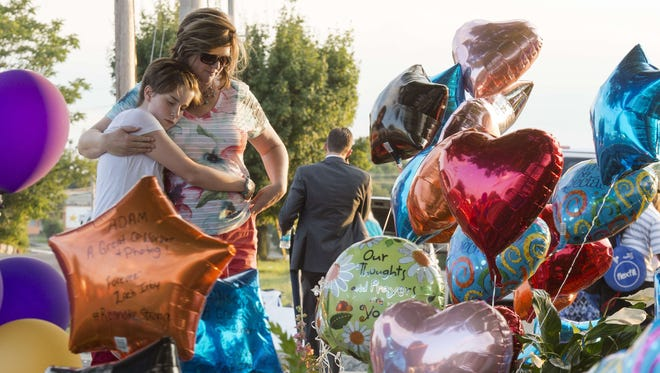A woman and her daughter pause after placing balloons at a make-shift memorial in front of WDBJ7-TV's studios on August 27, 2015, in Roanoke, Va.