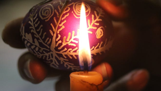 A candle is used to remove wax from an egg at St. Mary Protectress Ukrainian Church in Clifton.