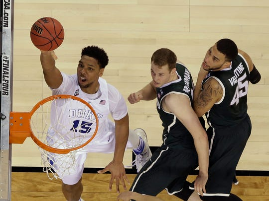 Duke's Jahlil Okafor goes up for a shot against Michigan State's Colby Wollenman and Denzel Valentine (45) during the second half of the NCAA Final Four tournament college basketball semifinal game Saturday, April 4, 2015, in Indianapolis.