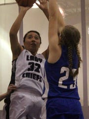 Mescalero's Katelyn Yuzos, left, puts up a shot while