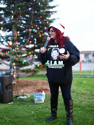 Debbie Aguilar, founder of A Time for Grieving and Healing, speaks Saturday during the Tree of Life lighting ceremony.