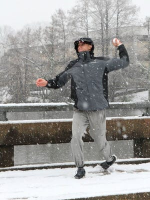 ULM center fielder Nathan Pugh trades a baseball for a snowball during the rare winter storm that hit the area this week.