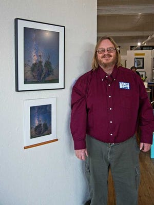 """Victor Gibbs stands with his award-winning photo, """"Yucca Under the Milky Way."""""""