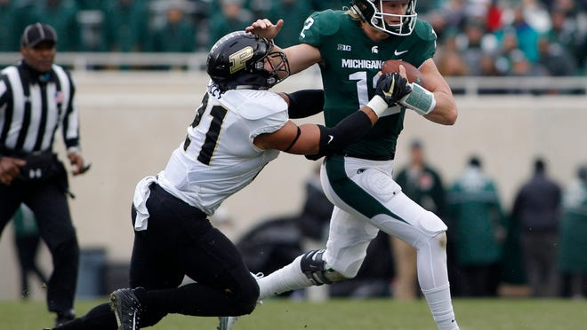 FILE - In this Oct. 27, 2018, file photo, Michigan State quarterback Rocky Lombardi, right, escapes from Purdue's Markus Bailey on a keeper during an NCAA college football game, in East Lansing, Mich. This isn't what Michigan State had in mind at the beginning of the season, but starting Rocky Lombardi at quarterback worked well enough last weekend in a win over Purdue. (AP Photo/Al Goldis)