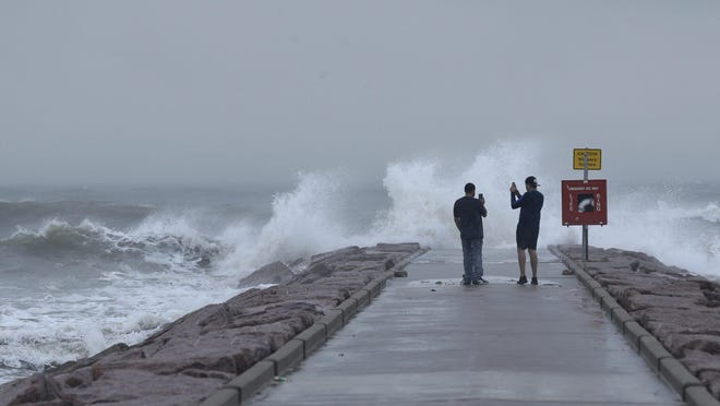 """CORRECTS DATE TO AUG. 26, 2020 INSTEAD OF AUG. 27, 2020- Josue Blanco, left, and Alex Mendez photograph waves generated by Hurricane Laura as they crash into the rock groin at 37th Street in Galveston, Texas on Wednesday, Aug. 26, 2020. Forecasters say Laura is rapidly intensifying and will become a """"catastrophic†Category 4 hurricane before landfall. It's churning toward Texas and Louisiana, gathering wind and water that swirls over much of the Gulf of Mexico."""