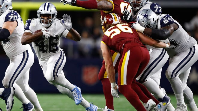 Alfred Morris #46 of the Dallas Cowboys tries to evade Ziggy Hood #90 of the Washington Redskins and Zach Vigil #56 of the Washington Redskins on a carry in the first half of a football game at AT&T Stadium on November 30, 2017 in Arlington, Texas.