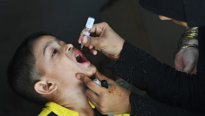 A Pakistani child receives polio vaccine drops during a polio vaccination campaign in Karachi on May 7, 2018. Pakistan is one of only two countries in the world where polio remains endemic.