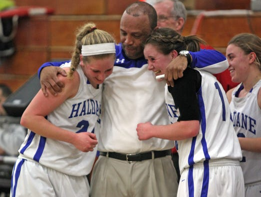 Haldane's coach Tyrone Searight hugs Jess Harrison (22) and Allie Monteleone (10) after defeating Friends Academy 46-38 during the Class C girls basketball regional finals at New Rochelle High School on March 8, 2014.