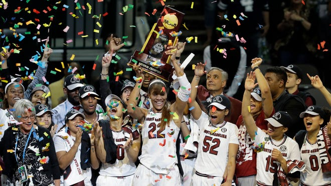 FILE - In this April 2, 2017, file photo, South Carolina forward A'ja Wilson (22) holds up the trophy as she celebrates with teammates after their win over Mississippi State in the final of the NCAA women's Final Four college basketball tournament, in Dallas. Reigning national champion South Carolina leaves behind last year's celebrations and starts preparations this week for a season the Gamecocks hope brings more trophies and cut-down nets their way.  (AP Photo/Eric Gay, File)
