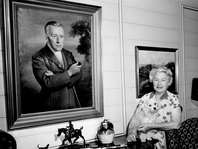 Sara Houghland is with a painting of her late husband, Mason Houghland, one of the founders of the Iroquois Memorial Steeplechase, May 5, 1964. Their son, Calvin, has ridden a winner in the Iroquois twice, and he has two horses in the feature race for the 23rd annual Iroquois Steeplechase.