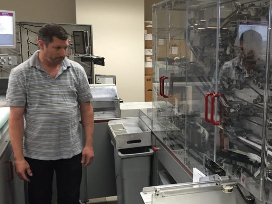 Jim Crawford, a processing assistant at First Data, watches an OPEX 150 mail extractor machine that sorts and scans payments at the company's Ogletown facility.