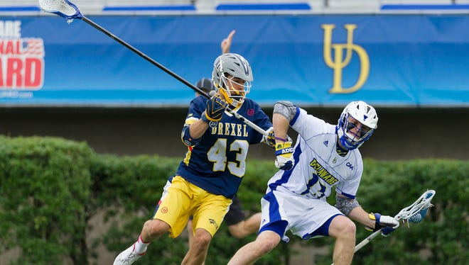 Dean DiSimone (#13) of UD works to get by Drexel's Jake Gennosa (#43) in the first quarter of UD vs Drexel men's lacrosse at Delaware Stadium on Saturday.