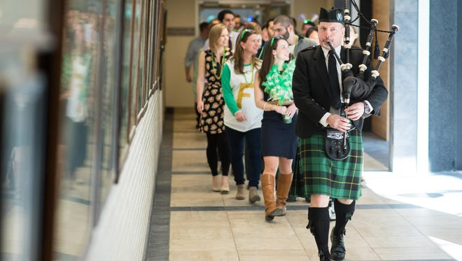 Radiation oncologist and bagpiper Dr. James Wallace leads Class of 2017 medical students down the Given Building hallway to the Match Day event at the Larner College of Medicine at the University of Vermont on Friday, March 17, 2017. Held annually the third Friday in March, Match Day is the day when graduating medical students learn the location and specialty of their U.S. residency program for the next three or more years.