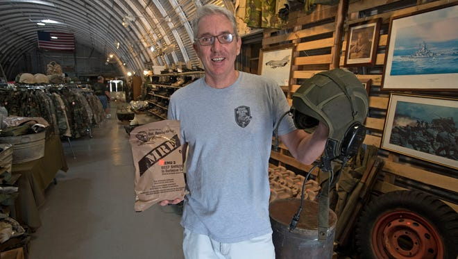 Owner Andy Tempesta shows off military memorabilia for sale at A Tin Hut Military Surplus on Navy Blvd.