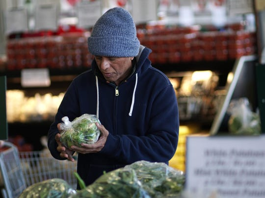 Raman Raja of Millsboro picks a bag of Brussels sprouts while shopping at Produce Junction in Dover.